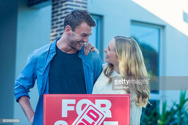 couple standing in front of a new home - mid adult stock pictures, royalty-free photos & images