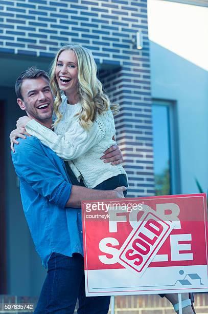 Casal em pé na frente de uma nova casa.