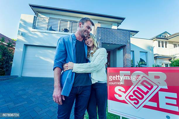 Couple standing in front of a new home.