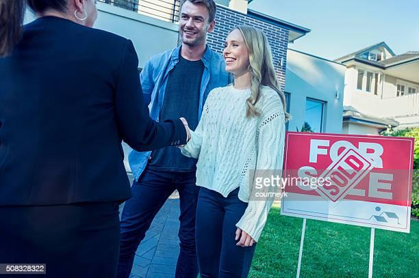 Paar stehend vor ein neues Zuhause mit Agent.