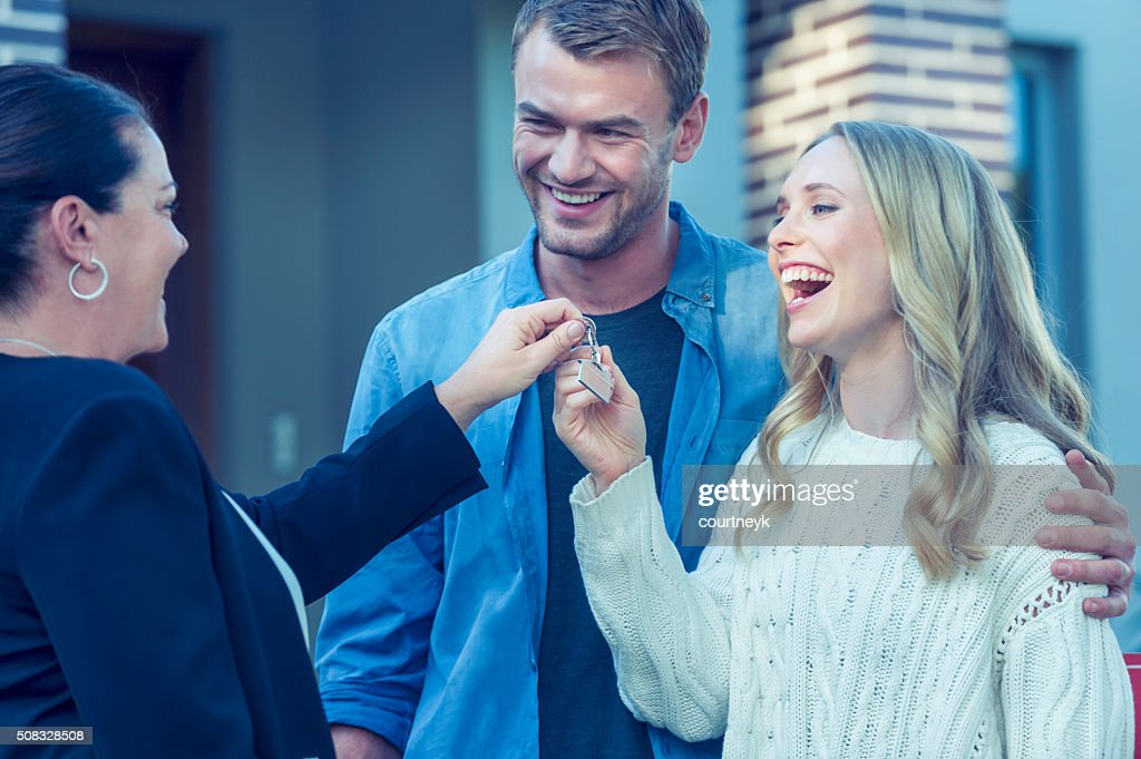 Couple standing in front of a new home with agent. : Stock Photo