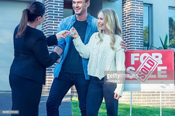Casal em pé na frente de uma nova casa com agente.