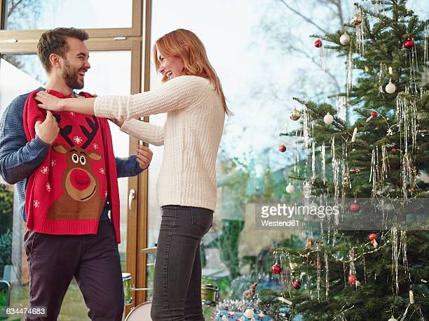 couple standing in front of christmas tree trying on christmas jumper - christmas jumper fotografías e imágenes de stock