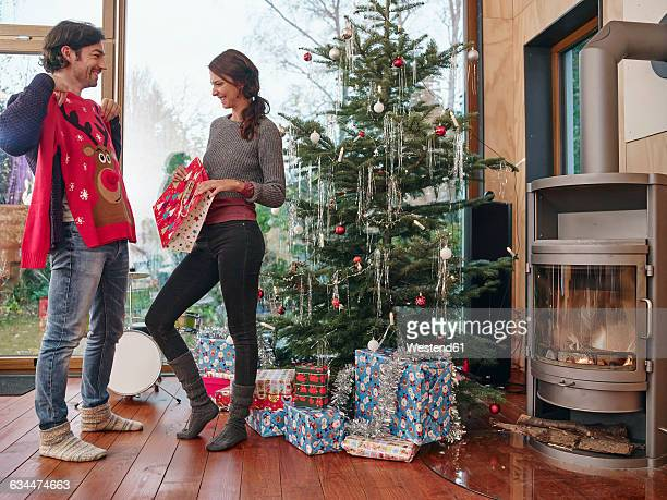 couple standing in front of christmas tree unwrapping christmas jumper - christmas jumper fotografías e imágenes de stock