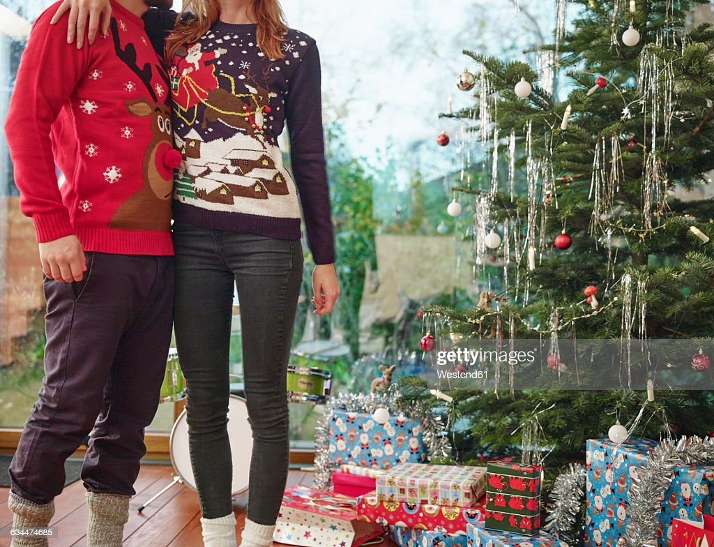 Couple standing in front of Christmas tree wearing Christmas jumpers : Stock Photo