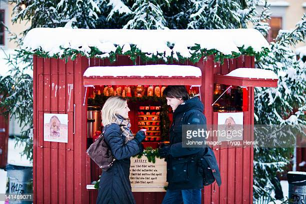Couple standing in front of food stall in snow