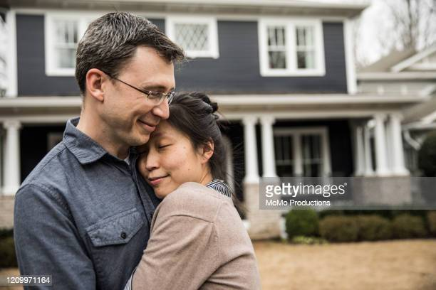couple standing in front of home - love stock pictures, royalty-free photos & images