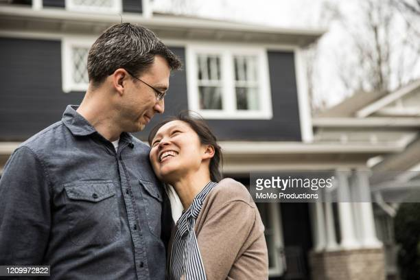 couple standing in front of home - home ownership stock pictures, royalty-free photos & images