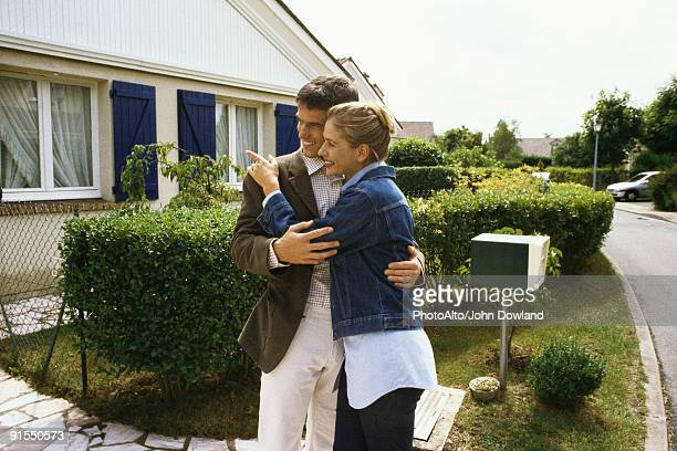 Couple standing in front of house, embracing
