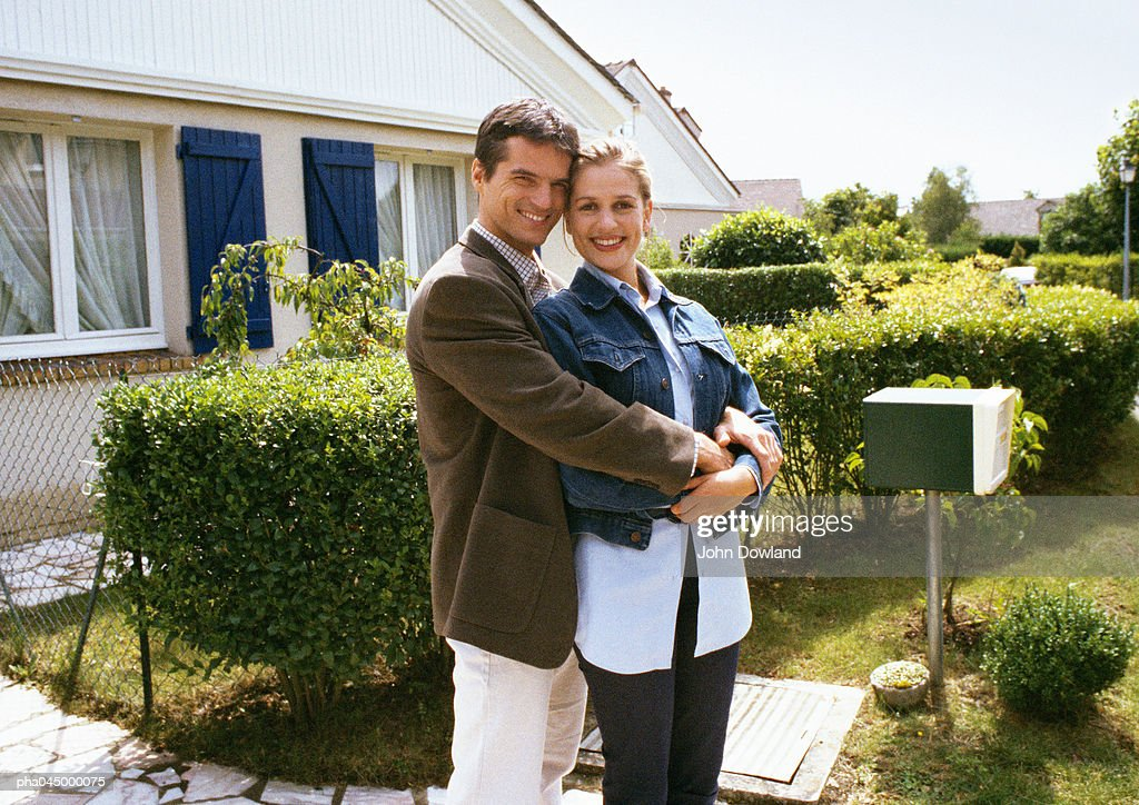 Couple standing in front of house, embracing : Stockfoto