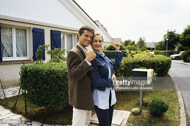 Couple standing in front of house, making thumbs up gesture at camera
