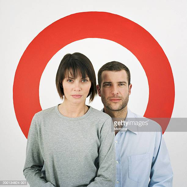 couple standing in front of red ring, portrait - microzoa stock pictures, royalty-free photos & images