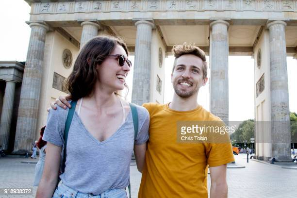 couple standing in front of the brandenburg gate brandenburger tor arm in arm - berlin stock pictures, royalty-free photos & images