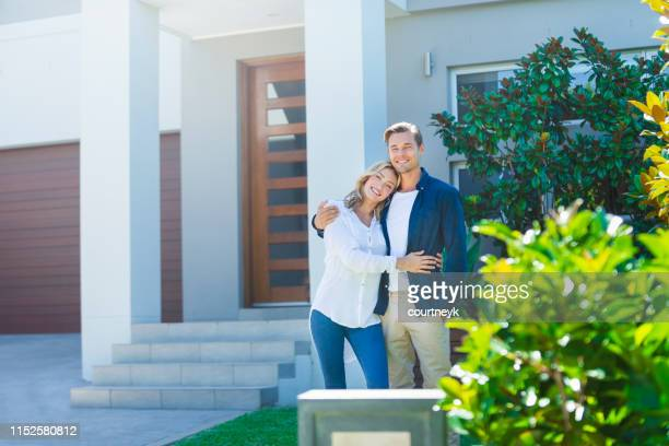 couple standing in front of their new home. - young couple stock pictures, royalty-free photos & images