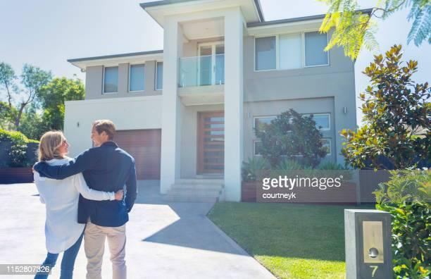 二人は新しい家の前に立っていた。 - 売り出し中 ストックフォトと画像