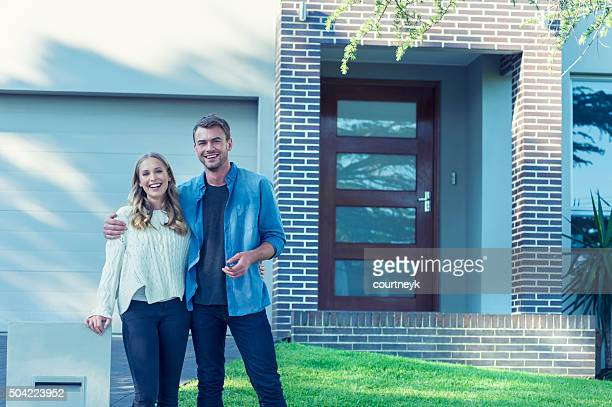 couple standing in front of their new home. - in front of stock pictures, royalty-free photos & images