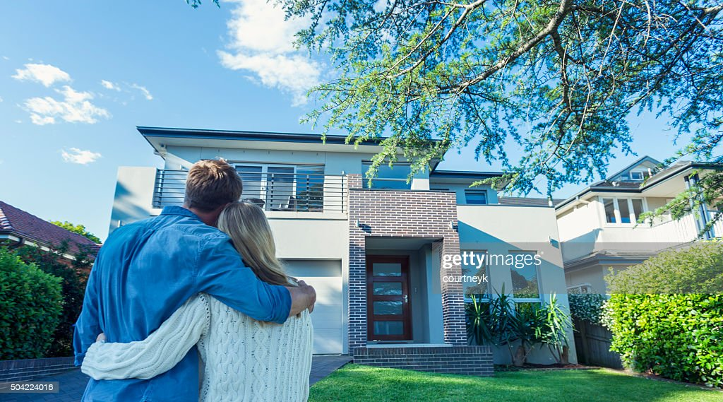 Couple standing in front of their new home. : Stock Photo