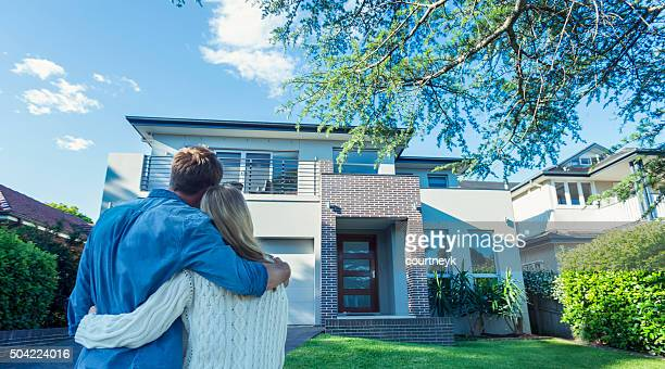 Couple standing in front of their new home.