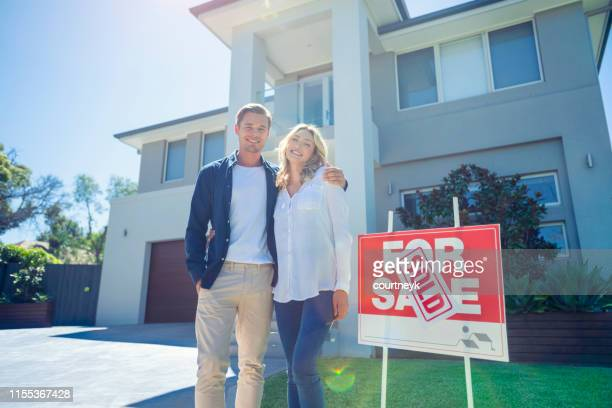couple standing in front of their new home with a for sale sign saying sold. - selling stock pictures, royalty-free photos & images
