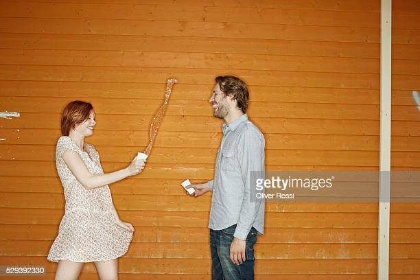 Couple standing in front of wooden wall and splashing water from disposable cups