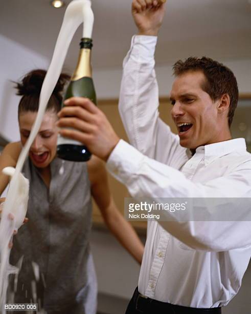 Couple standing in kitchen, man holding opened champagne bottle