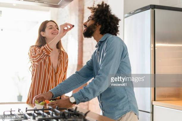 couple standing in kitchen, preparing dinner party, woman feeding man with olive - man eating woman out stock photos and pictures