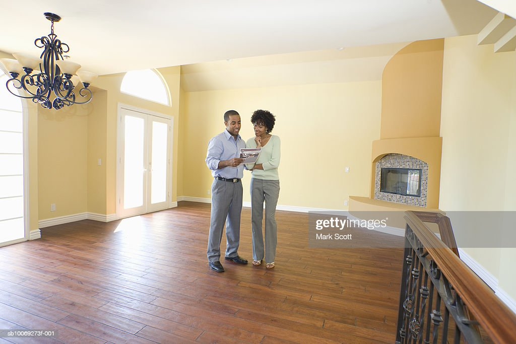 Couple standing in new home reading real estate leaflet : Stockfoto