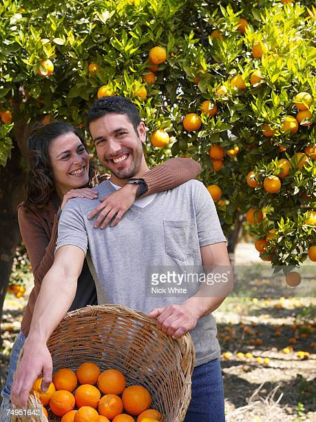 Couple standing in orange orchard, smiling, portrait