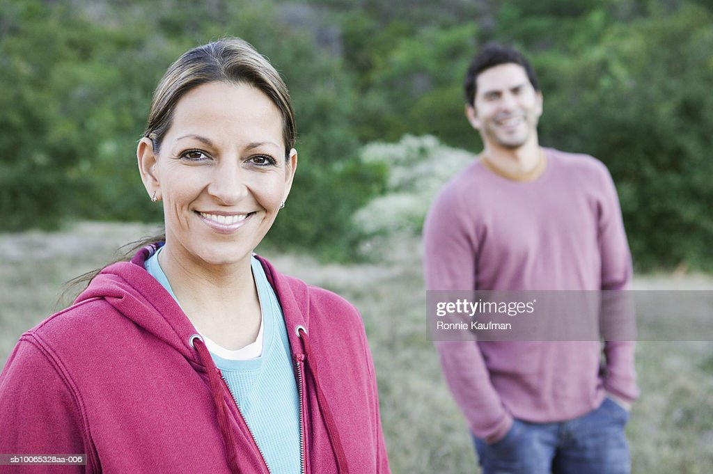 Couple standing in park, smiling : Foto stock