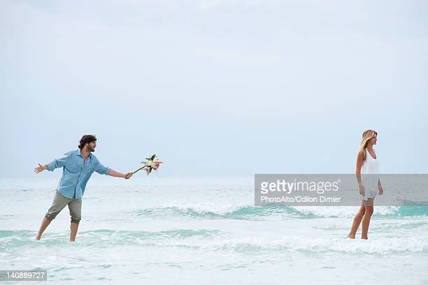 Couple standing in sea, woman walking away from man as he holds out a bouquet