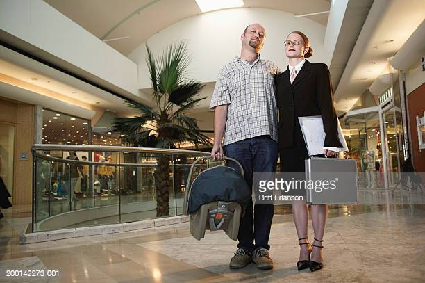 couple standing in shopping mall, man holding baby carrier, portrait - 主夫 ストックフォトと画像