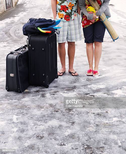 couple standing in snow with suitcases - froid humour photos et images de collection