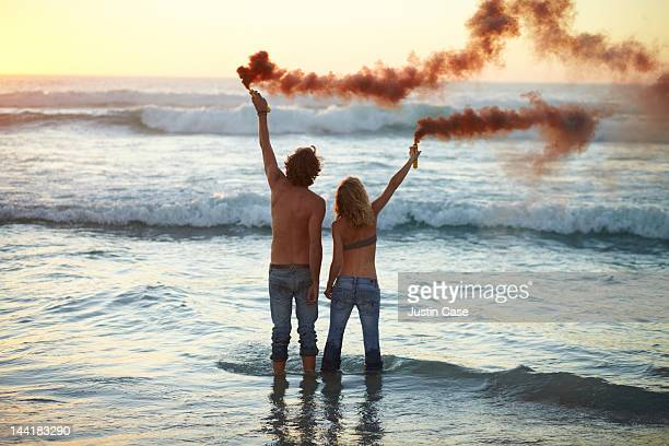 Couple standing in the ocean with smoke grenades