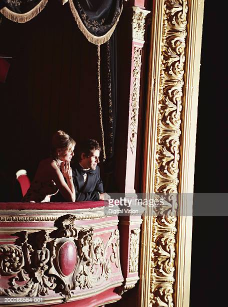 Couple standing in theatre box, leaning on cushioned ledge, side view