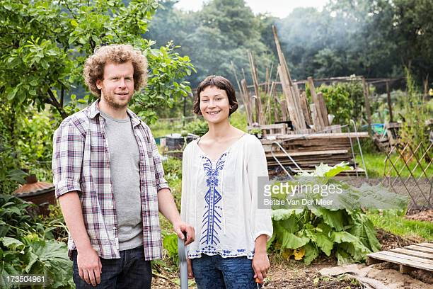 Couple standing in vegetable plot in allotment.
