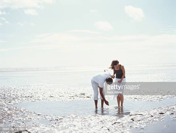 couple standing in water pool on beach, man stooping to splash water - bending over in skirt stock pictures, royalty-free photos & images