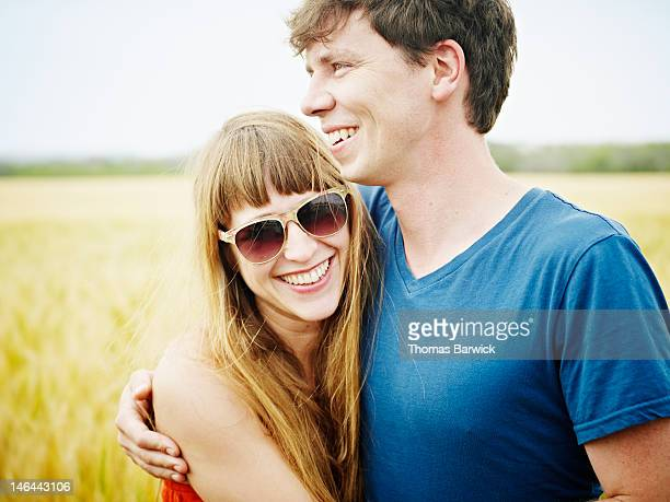 couple standing in wheat field embracing smiling - sleeveless top stock pictures, royalty-free photos & images