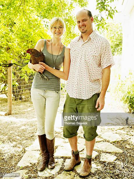 Couple standing in yard woman holding pet hen