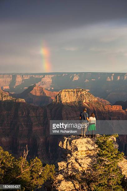 A couple standing looking at a rainbow and grand canyon landscape.