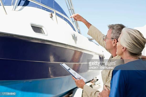 couple standing near a yacht with a brochure - onoky stock-fotos und bilder