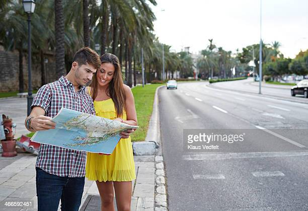 Couple standing near big street, looking at map