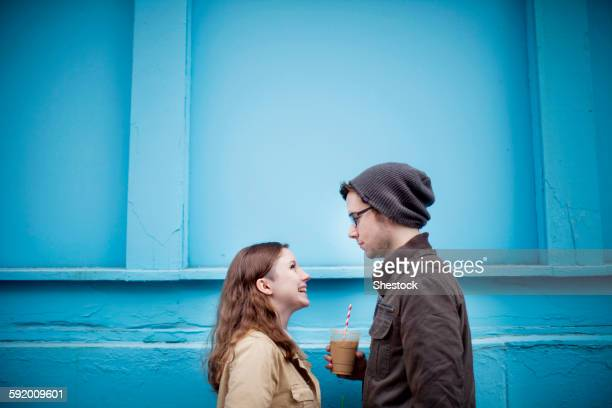 couple standing near blue wall - toned image stock pictures, royalty-free photos & images