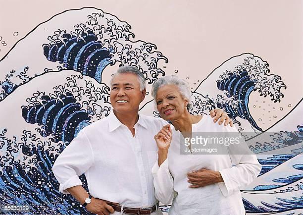 Couple standing near mural of ocean waves