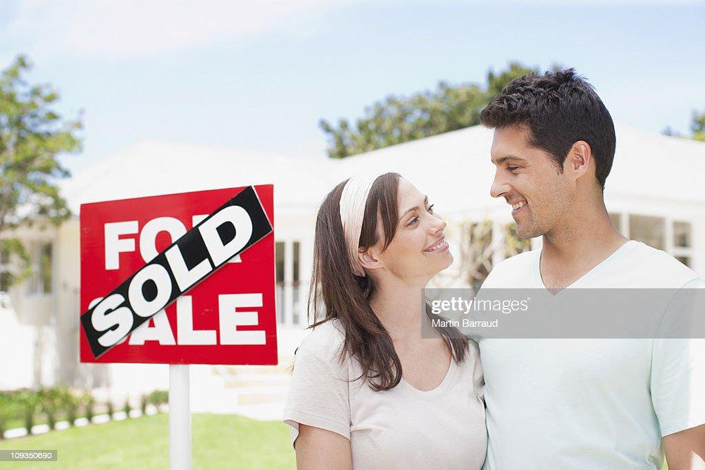 カップルの近くに立つ販売サインの新しい家 : ストックフォト