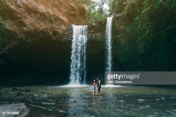 Couple  standing  near  Tibumana waterfall in Bali, Indonesia