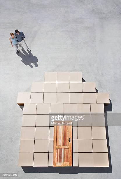 Couple debout à côté de maison en contour sur le trottoir