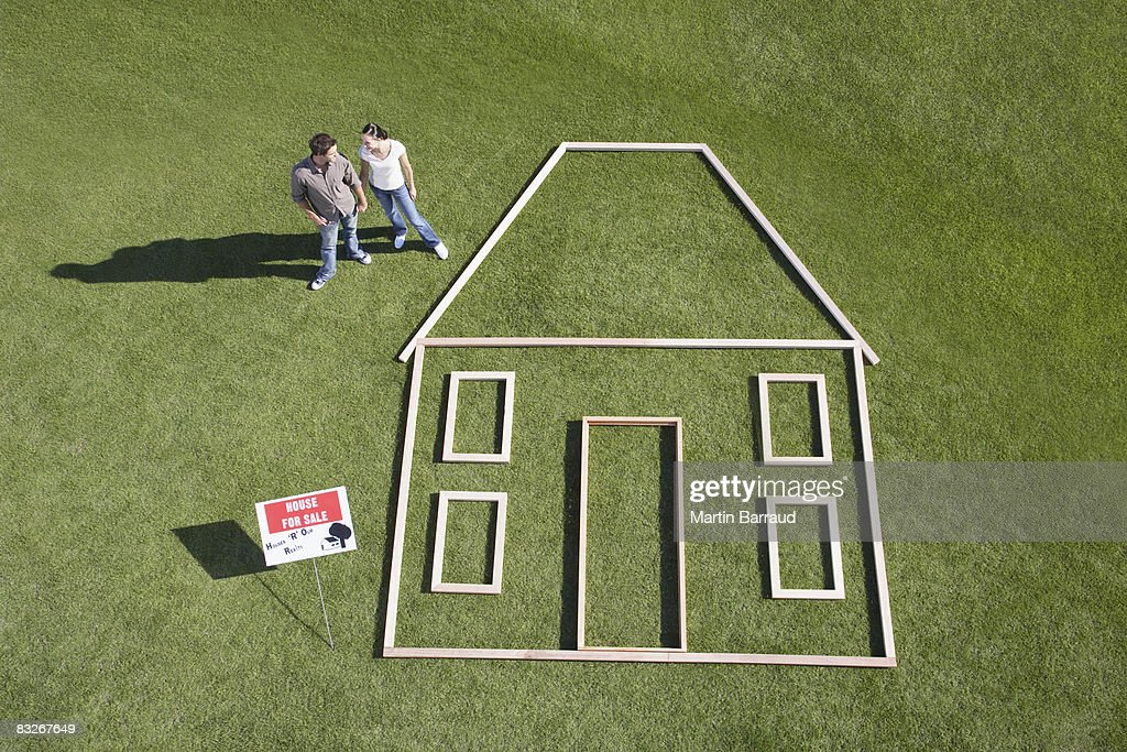 Couple standing next to house outline : Stockfoto
