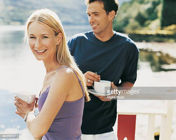 couple standing on a balcony beside a lake holding cups - next to stock pictures, royalty-free photos & images