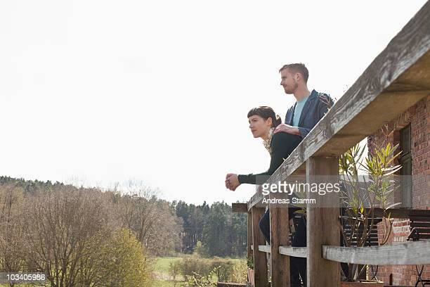 A couple standing on a balcony looking into the distance