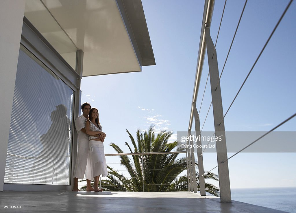 Couple Standing on a Coastal Apartment Balcony Looking at the View : Stock Photo